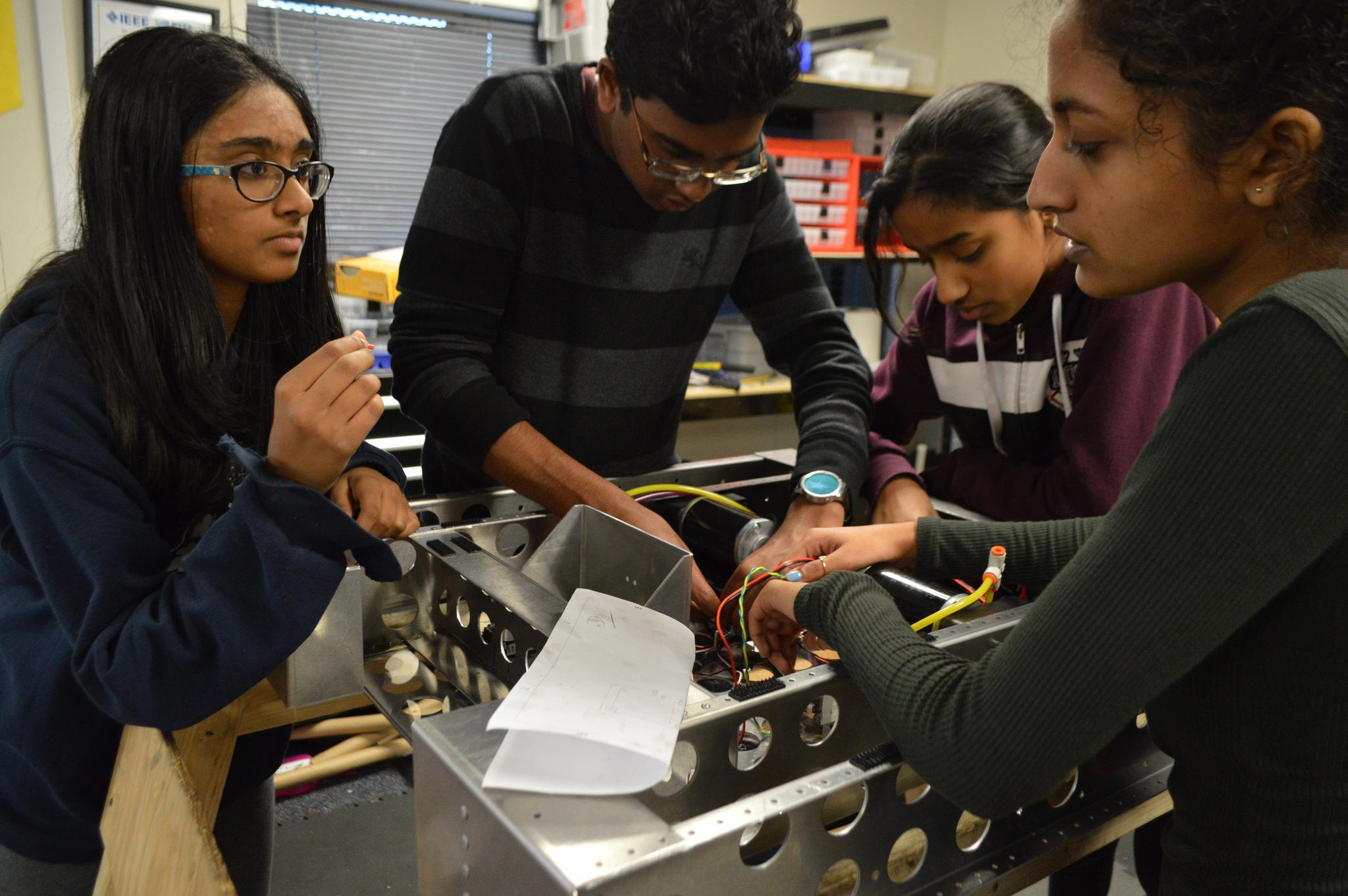 Palla works with three female members to adjust components of the robot. This year, MVRT aims to encourage girls to participate equally throughout the build season.