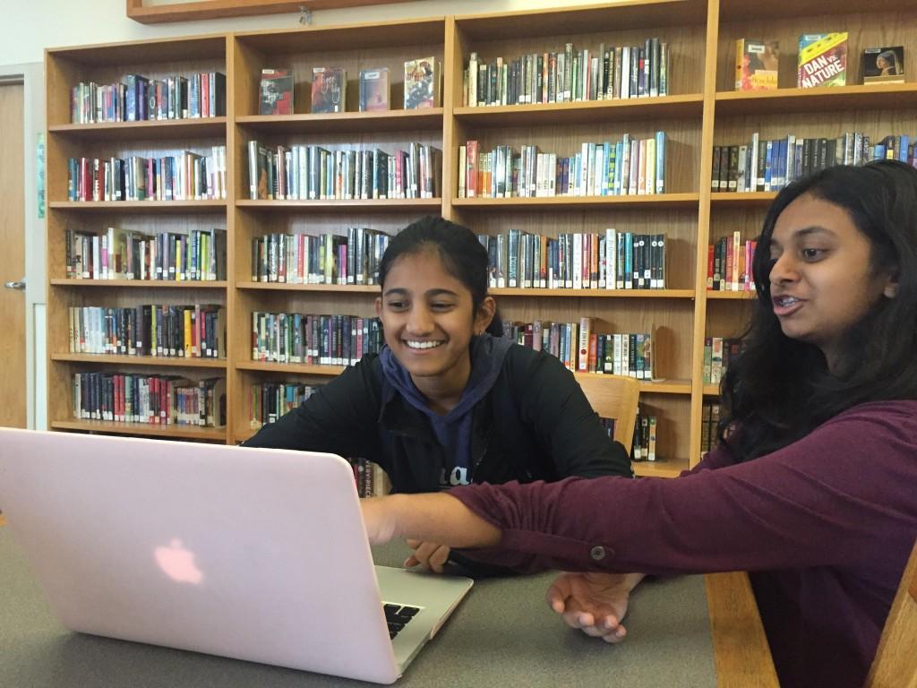 Sophomore+Pratya+Poosala+describes+her+virtual+pig+dissection+to+freshman+Sravya+Kari.+Photo+by+Sreya+Kumar.