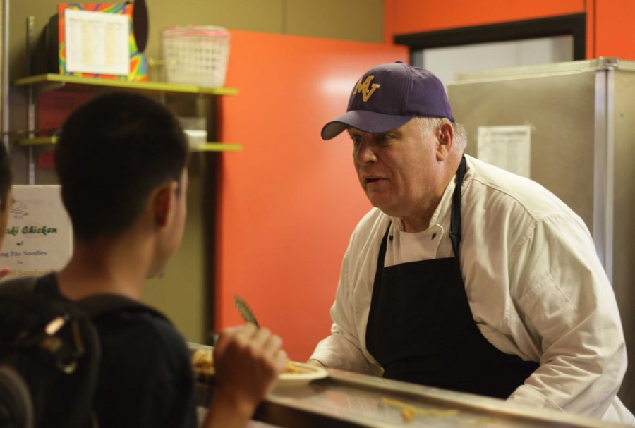 """Food Services Supervisor Frank Lihn serves Kung Pao Noodles to students on Thursday Aug. 25, otherwise known as """"Stir Fry Day."""" According to Lihn, his food station in the cafeteria pushes an average of 150 students through per day. Photo by Kevin Tsukii."""
