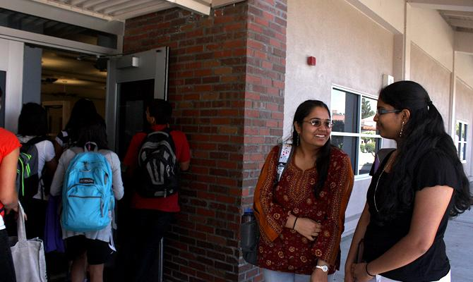 Sophomores Sneha Bolineni and Sai Morramreddi watch as a class enters the library during fourth period. Although they have yellow cards, they are unable to enter as the library is only open to classes this week. Photo by Angela Liu.