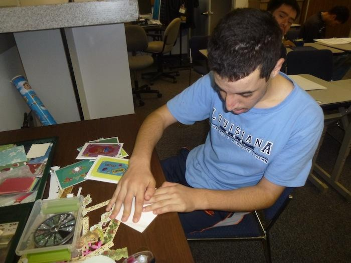 A Bridges program student assembles holiday cards, which cost $2 each. According to Bridges teacher Laurie McClelland, this is the first year that the program has adopted card-making as a method of reaching out to the community. Photo used with permission of Laurie McClelland.