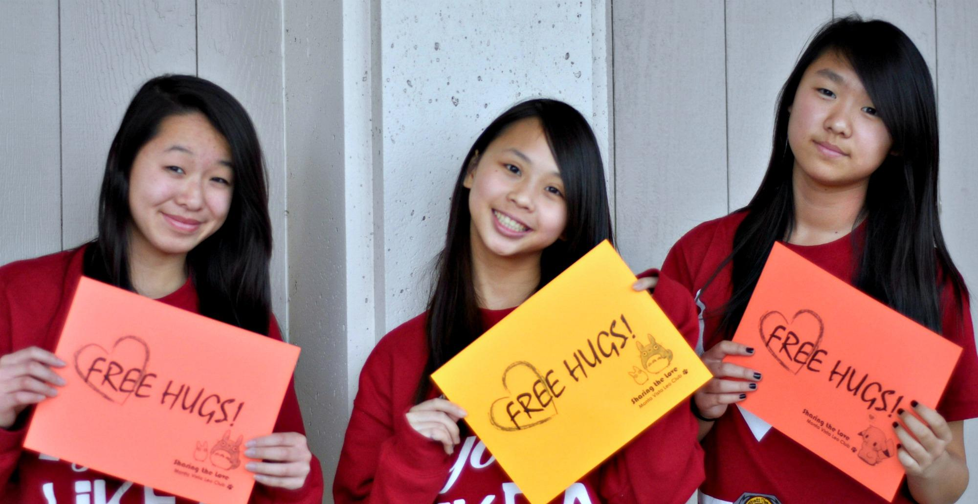 "President senior Tiffany Wu, Director of Events sophomore Jessica Ho, and Director of Projects sophomore Alice Ma (from left to right) show off their ""Free Hugs"" signs that will be used on Friday. ""I think it's just to tell people to appreciate the people around us,"" Wu said. ""Even in our own community here, there is a lot we can do to help. And a small token of appreciation can go a long way."" Photo by Karishma Mehrotra."