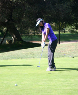 Sophomore Valene Tjong attempts to putt a ball into the fourth hole at Cupertino's Deep Cliff Golf Course. Tjong finished with a score of 55. Photo by Karen Feng.