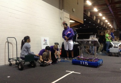 MVRT president senior Evelyn Ding, pit members sophomores Andrew He and RJ Cunningham and engineering lead senior Kumar Veeravel calibrate the robot on the practice field before competition at the Sacramento Regional. A lack of testing during the build season led to physical faults during the qualification matches that kept the team from being picked for quarterfinals. Photo by Karen Feng.