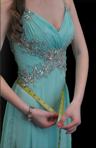 Girl in prom dress measures her waist.