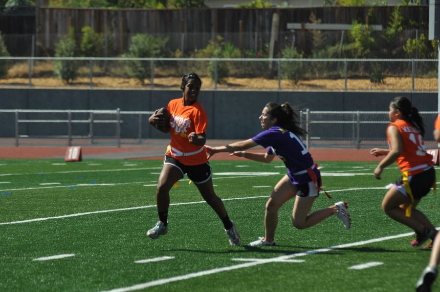 Senior Amy Spelick chases down freshman Kirthi Gomatam in order to get a sack in last year's powderpuff. This year Powderpuff will not be at the same time as the homecoming celebrations. Photo by Margaret Lin.