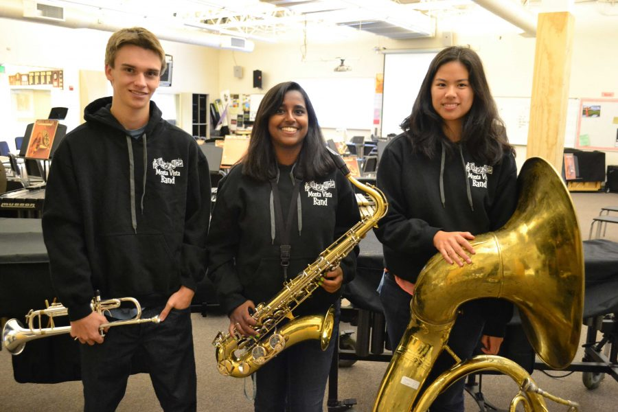 Seniors Mike Thomas, Anu Vaishnav and Connie Guan display their instruments and matching band sweatshirts. With the cancellation of the program, they will lose the experience of competing as marching band this year. Photo by Yashashree Pisolkar.