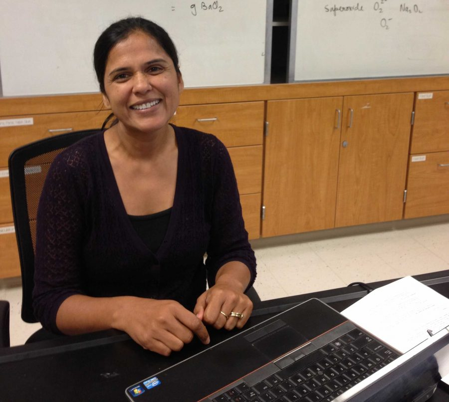 Kavita Gupta sits at her desk in her AP Chemistry classroom. AP Chemistry students used her iBook in class to learn and quiz themselves on the lesson. Photo by Lydia Seo.