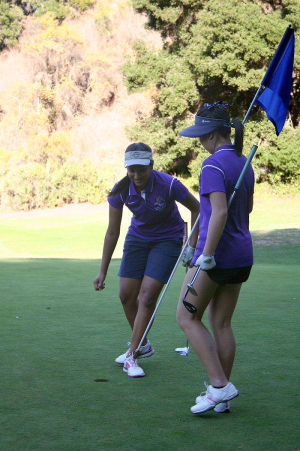 Senior co-captain Natalie Ng picks up the flag at the fourth hole for senior co-captain Shruthi Perati at their match against Gunn High School on Oct. 17 at Deep Cliff Golf Course. Ng will likely attend the SCVL championships on Oct. 22 due to her 20th seed ranking before the match. Photo by Karen Feng.
