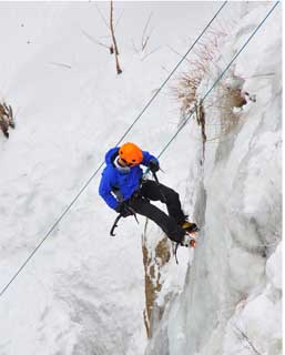 Junior Andrew Stewart ice climbs during the Ouray Ice Festival in Colorado
