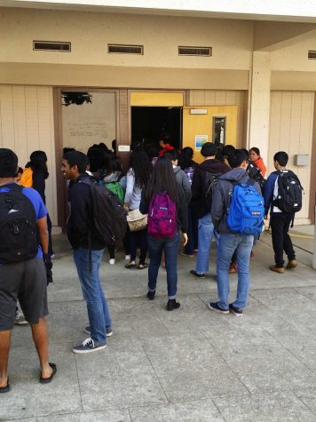 While chatting amongst themselves, students are patiently waiting for their teacher to unlock the classroom door.