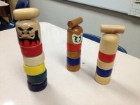 Three daruma-otoshi pieces stand menacingly on the desk. How to play Daruma-Otoshi: take out the small gavel on top and try to knock out a round wooden piece below without tumbling the small tower. Photo by Yifei Wu.