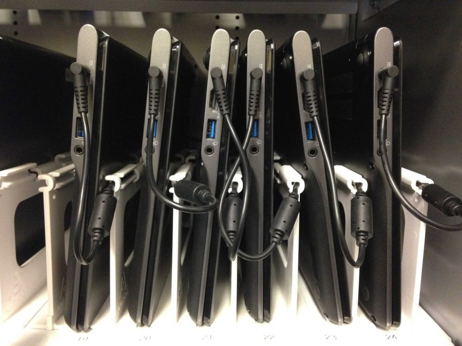 "Mini chromebooks are arranged and plugged into the built-in chargers on a shelf inside of a chromebook cart. The implementation of these technologies is a contributing factor as to why MVHS has become a ""Google school"". Photo by Neha Patchipala"