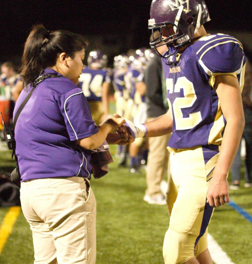 Athletic+trainer+Marie+Gishifu+bandages+a+deep+cut+Junior+James+Midgal+got+during+MVHS%E2%80%99+homecoming+game+again+against+PAHS.+Photo+by+Trisha+Kholiya.+++