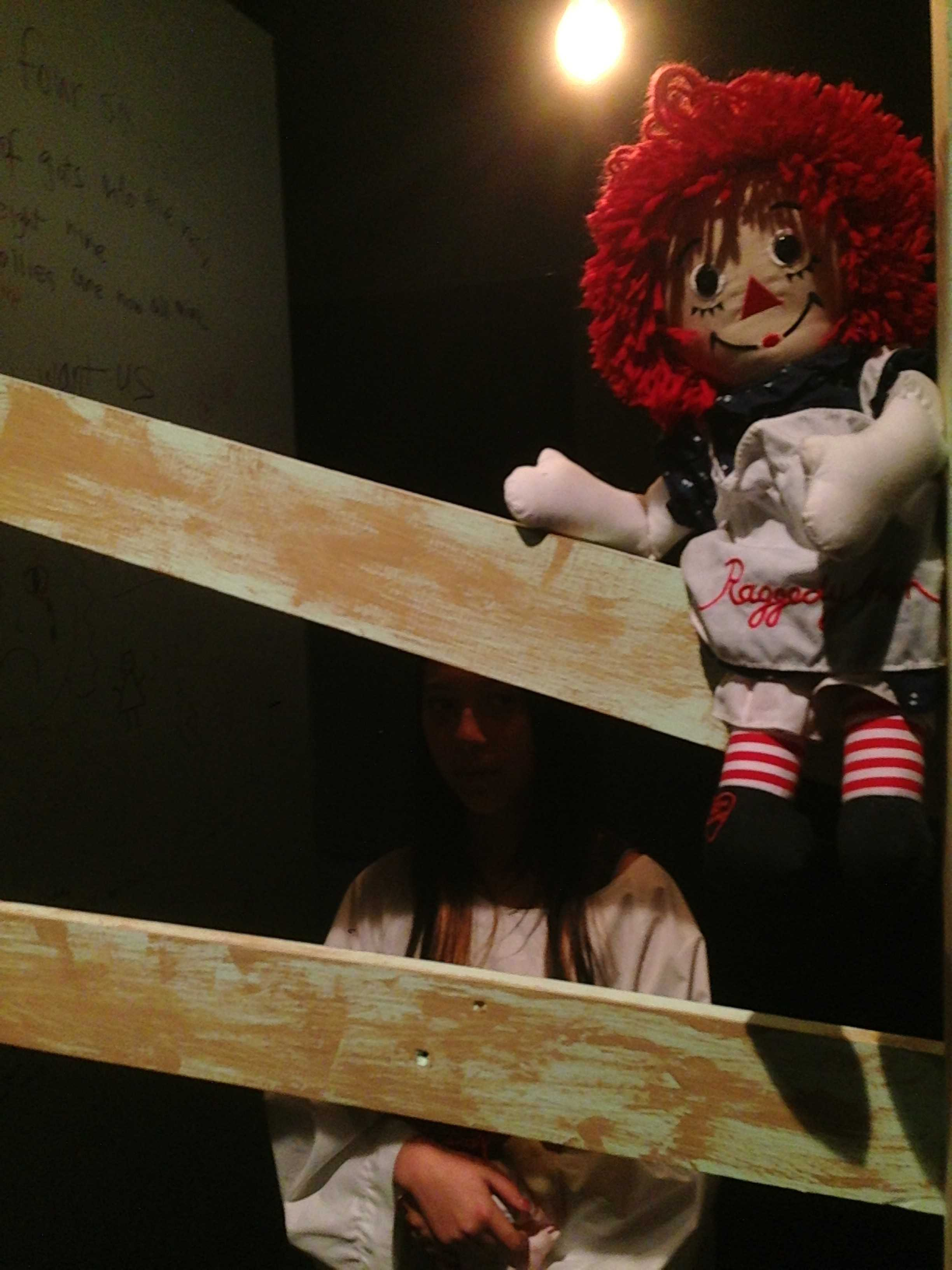 """An asylum patient stands in her boarded-up stall, next to a wall covered in """"bloody"""" writing. The Drama students practiced to immerse themselves in their insane characters' roles. Photo by Rhonda Mak."""