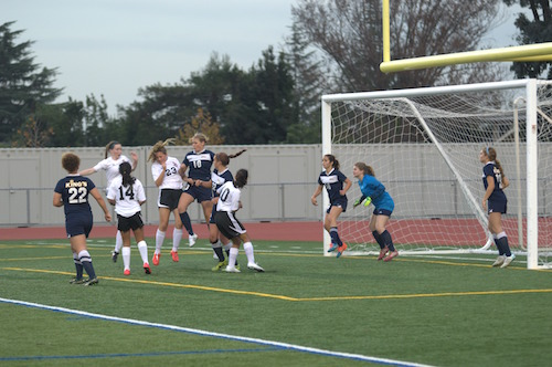 Freshman Nina Biondi collides with a player from Kings Academy as she reaches for the ball following a corner kick. The Knights had several chances to score a goal following corner kicks, but missed each time, with the ball hitting the edge of the goal post instead. Photo by Varsha Venkat.