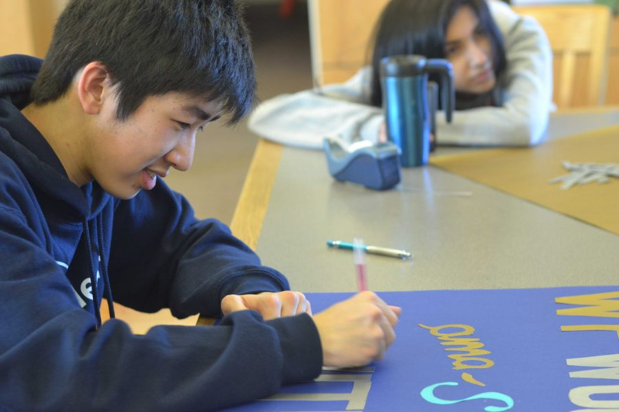 Art Club treasurer sophomore Patrick Zhou works diligently on finishing a Winter Formal poster after school on Tuesday, Jan. 20, in the MVHS Library. The poster-making project has built a stronger sense of community and fostered member bonding within Art Club. Photo by Mingjie Zhong.