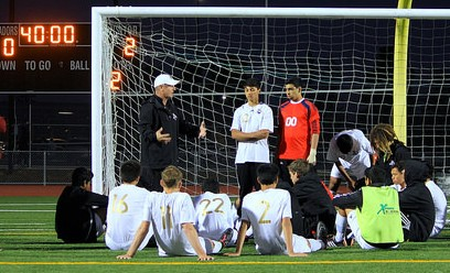 Boys soccer players listen to coach Patrick Lowney during halftime on Feb. 17. The team was down 2-0 against Mountain View High School halfway through the game.