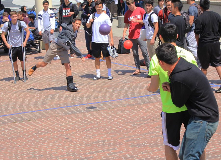 Despite a foot injury, senior Greg Moe flings a dodgeball at seniors Casey Parsay and Danny Takahashi on April 20. Photo by Justin Kim.