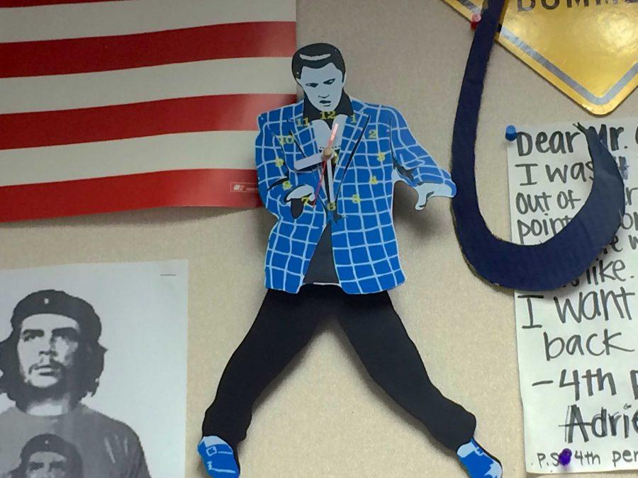 A broken Elvis clock is one of the many objects on Clarke's classroom walls. Photo by Amita Mahajan.