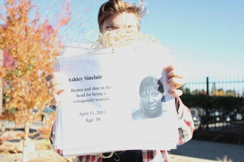 Senior Nikki Stuart, co-president of GSA, holds the banner that they will display during the vigil. The banner has the photos and stories of transgender people who were murdered or committed suicide. Photo by Sneha Gaur.