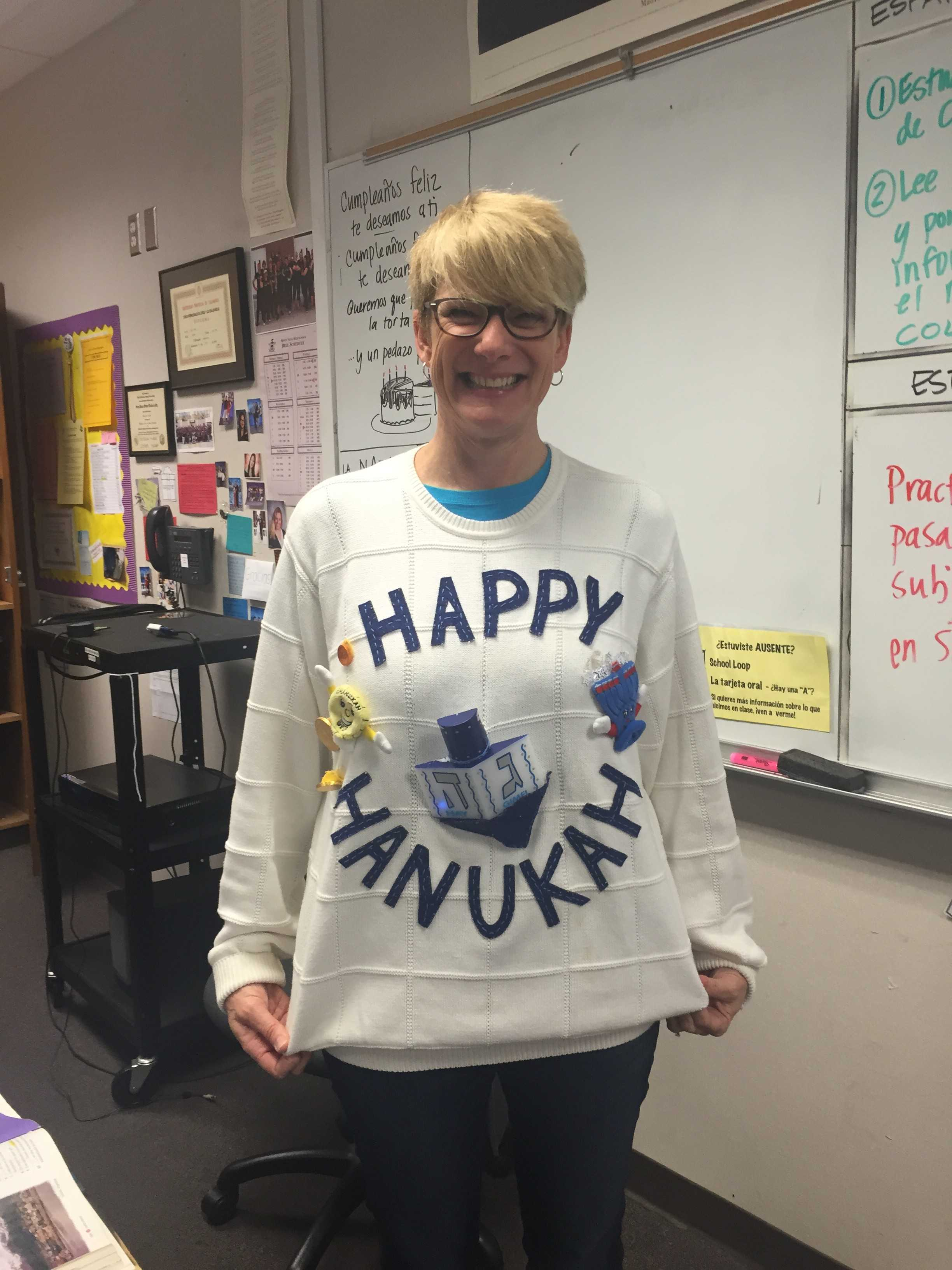 "Guadiamos proudly showcases her creative ugly sweater. The sweater is plain white with different objects stuck onto it and the words ""Happy Hanukkah"" are slathered across in big indigo letters."