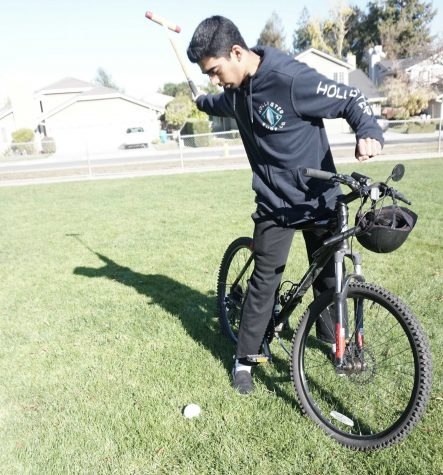 Senior Sid Sharma demonstrates a forehand shot, using his bike as a mock horse. In order to perform shots in polo, Sharma learned how to stand on a galloping horse.