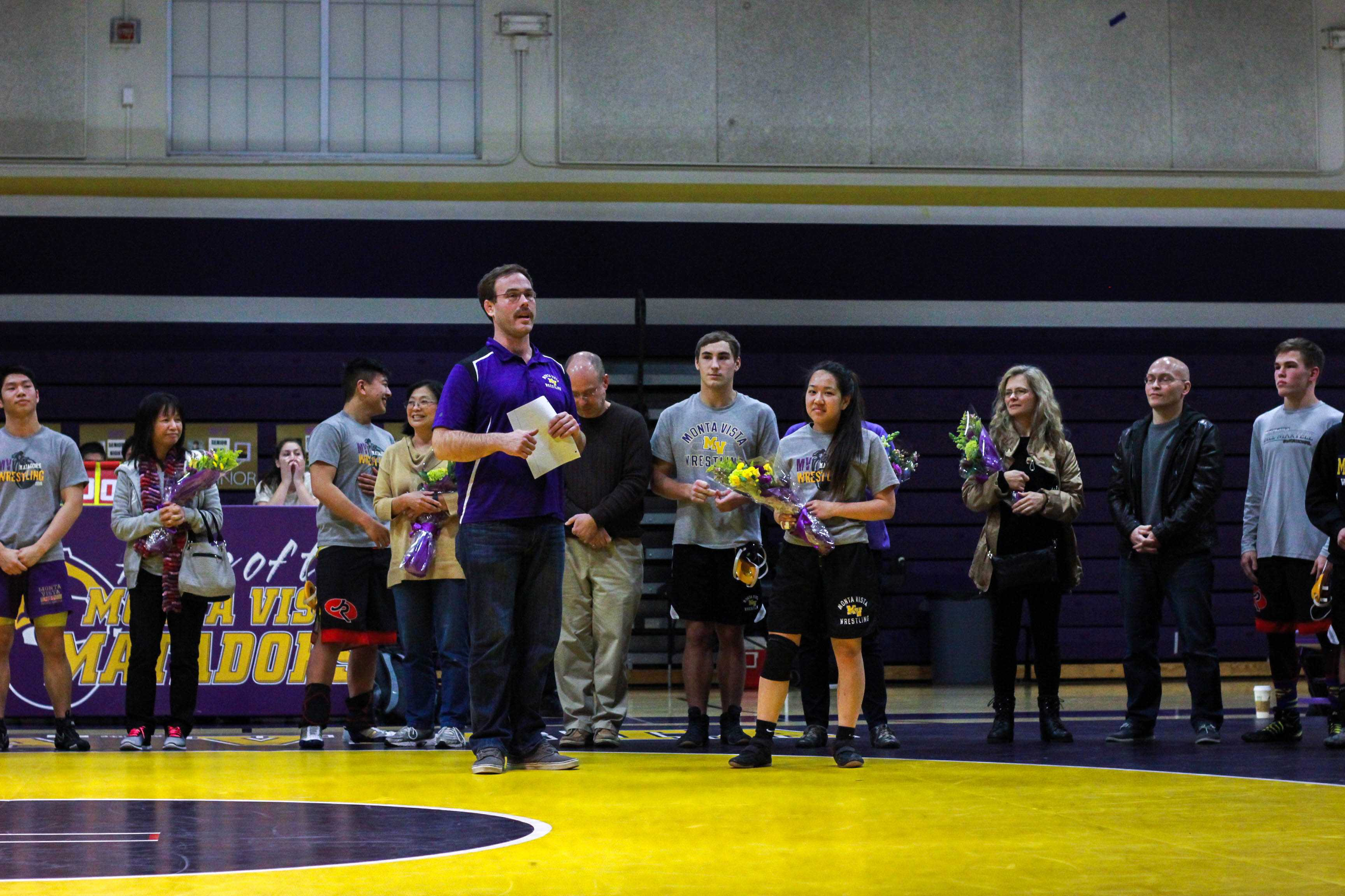 All the seniors line up on the wrestling mat after the JV matches. Senior night gave recognition to the seniors. Photo by Vanessa Qin.