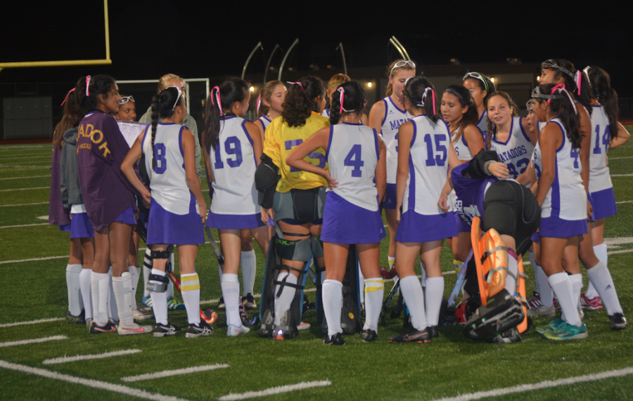 The players gather in a huddle after the game. Despite the results, they felt they played well as a team.