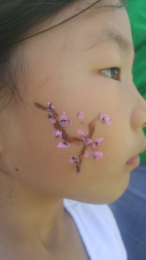 People+arrive+at+the+festival+and+receive+a+hand-painted+cherry+blossom+branch+on+their+cheek.