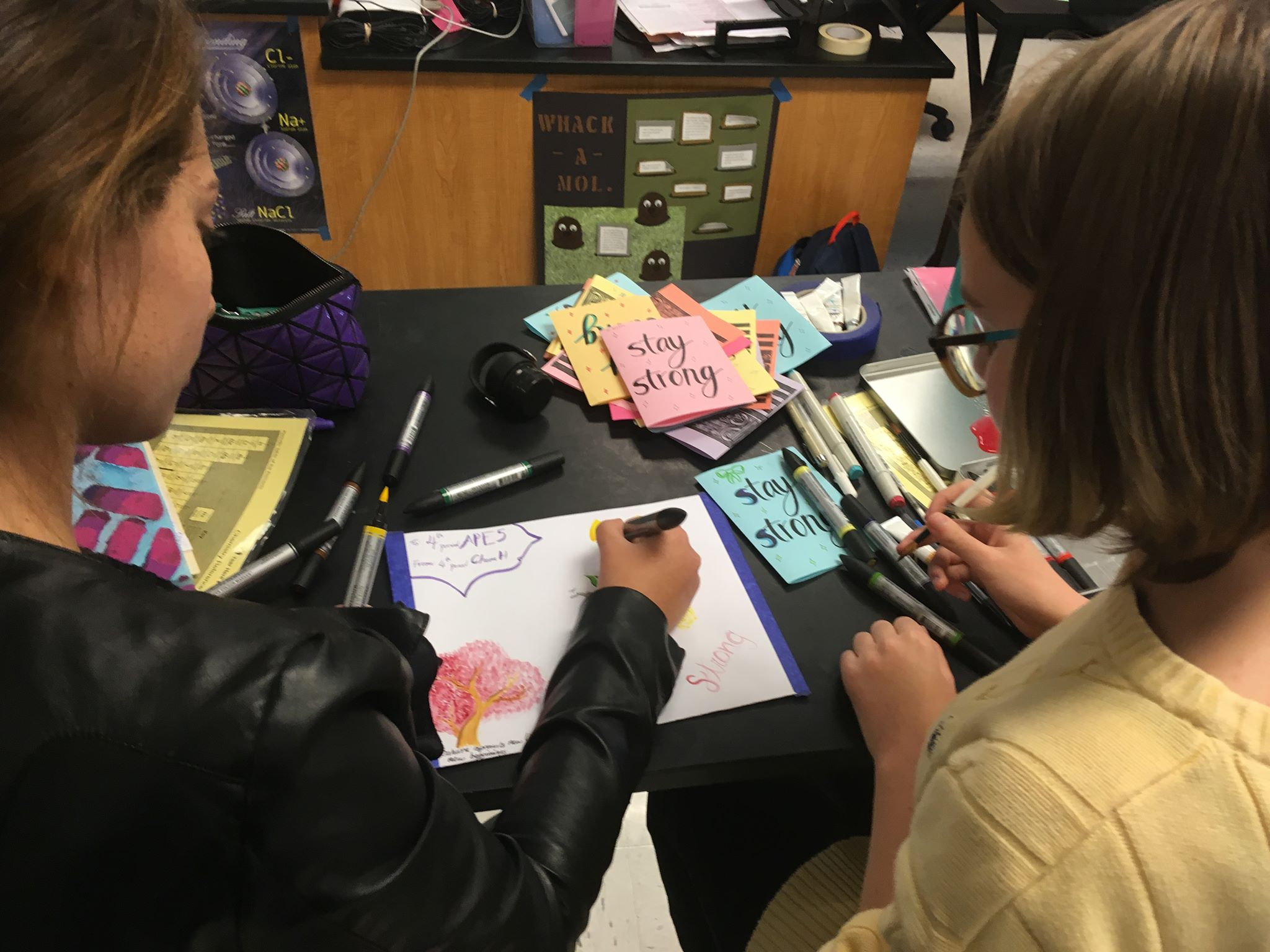"""Students write letters to the Parkland survivors on colorful pieces of paper decorated with the phrases """"Stay Strong"""" and """"Persevere."""" They then put the paper into a handmade, colorful envelope, ready to be sent to the MSDHS students. Photo by Sreya Kumar."""