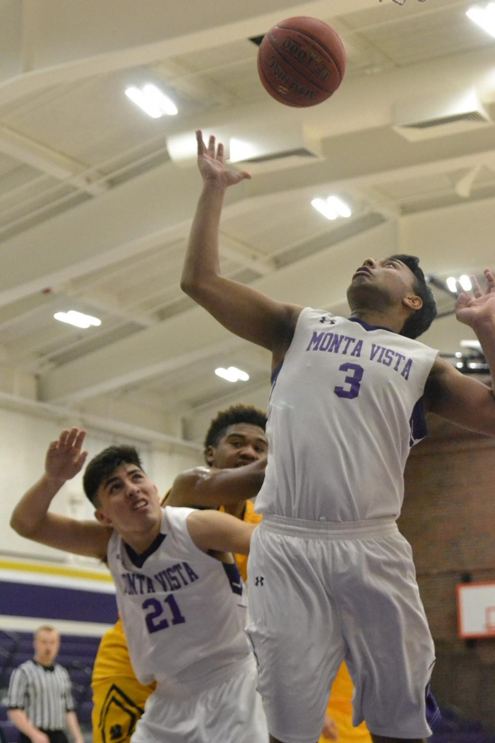 Junior Arvind Jagdish reaches up for a rebound as senior Josiah Figueroa covers him. Photo by Brandon Ng.