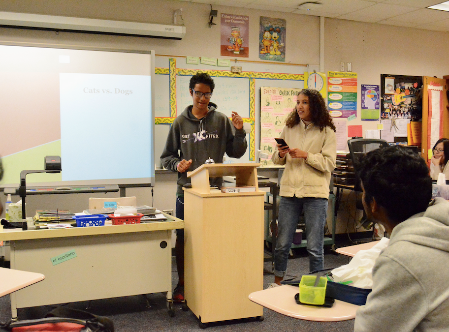 Sophomores Claudia Maldonado and Siddhant Patel present their argument to the rest of the Spanish Honors Society. Photo by Brandon Ng.