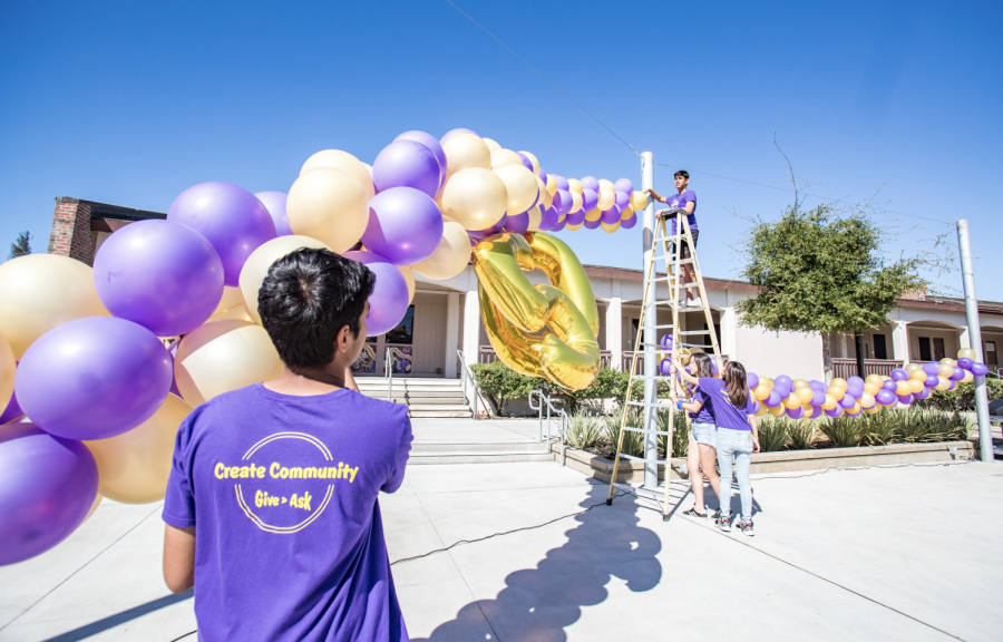 Members+of+Leadership+help+set+up+the+stage+by+hanging+up+a+purple+and+gold+balloon+arches+where+dance+and+music+performances+were+held.+