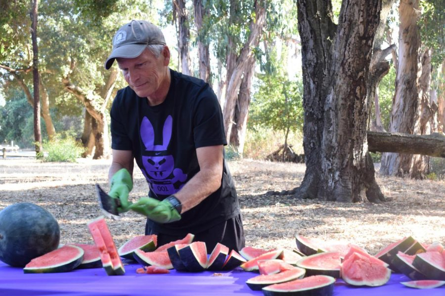 As+more+runners+gravitate+toward+the+tables+after+completing+the+annual+Watermelon+Run%2C+Coach+Kirk+Flatow+slices+watermelon+to+serve+as+a+sweet+treat.+