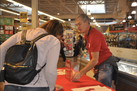 Patrick Wyman informs a customer about the We Love Local event and how to receive a free bag.