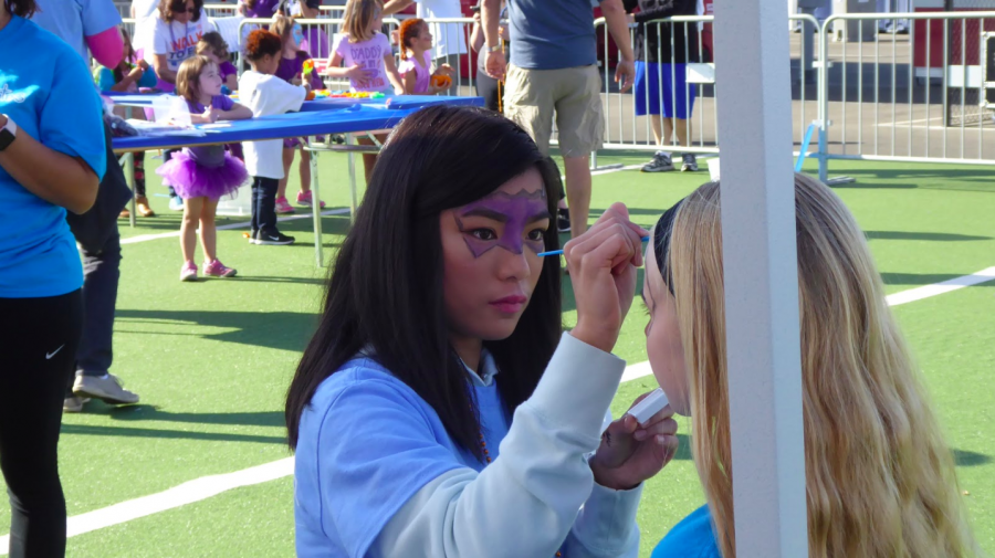 An Octagon volunteer paints a child walker's face in light of the JDRF marathon. Photo by Trudy Esrey // Used with permission