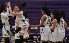 Senior Jocelyn Chang jumps up and high fives her teammate in their warm up lines as they get set to play Santa Clara HS in their home opener. Photo by Anish Vasudevan