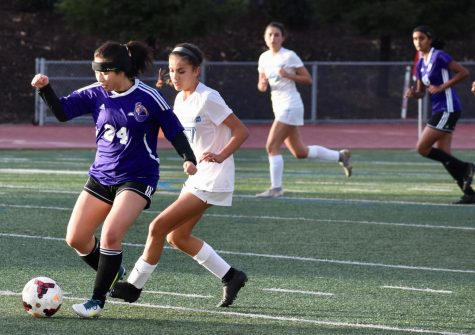 Senior Jaimie Chan tries to shield the ball against a VCHS player.