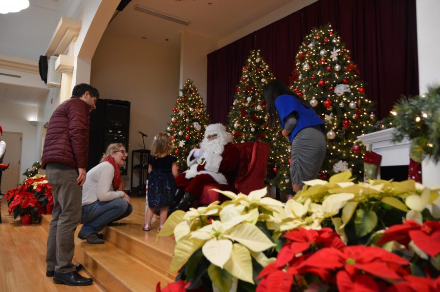 A child communicates with Santa as ASL interpreter Darlene Rochkind provides additional encouragement.