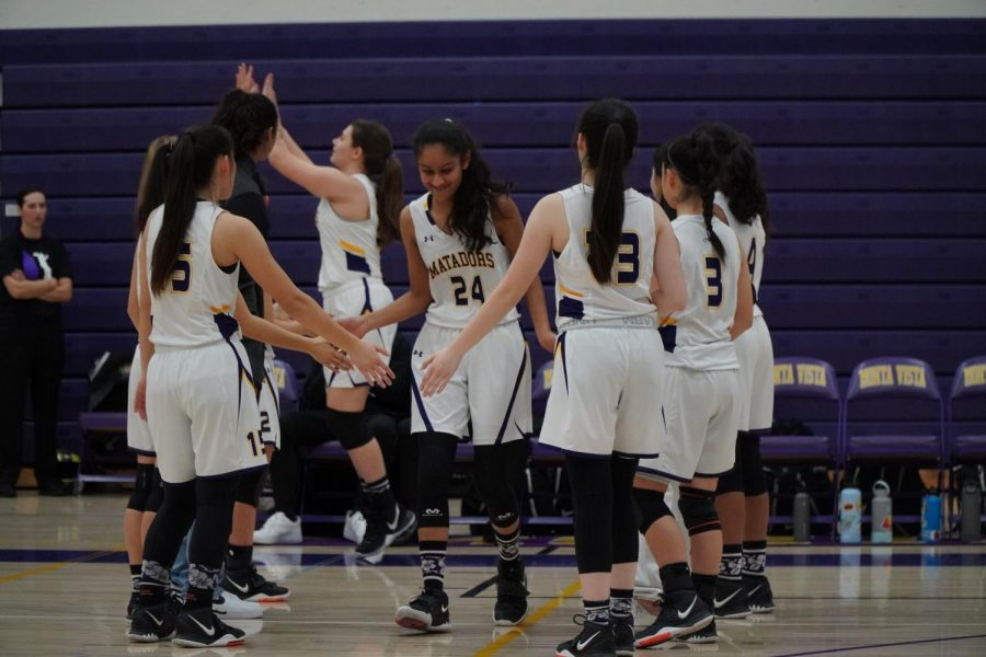 Junior Eshani Patel high-fives her teammates during the team introduction before the game.