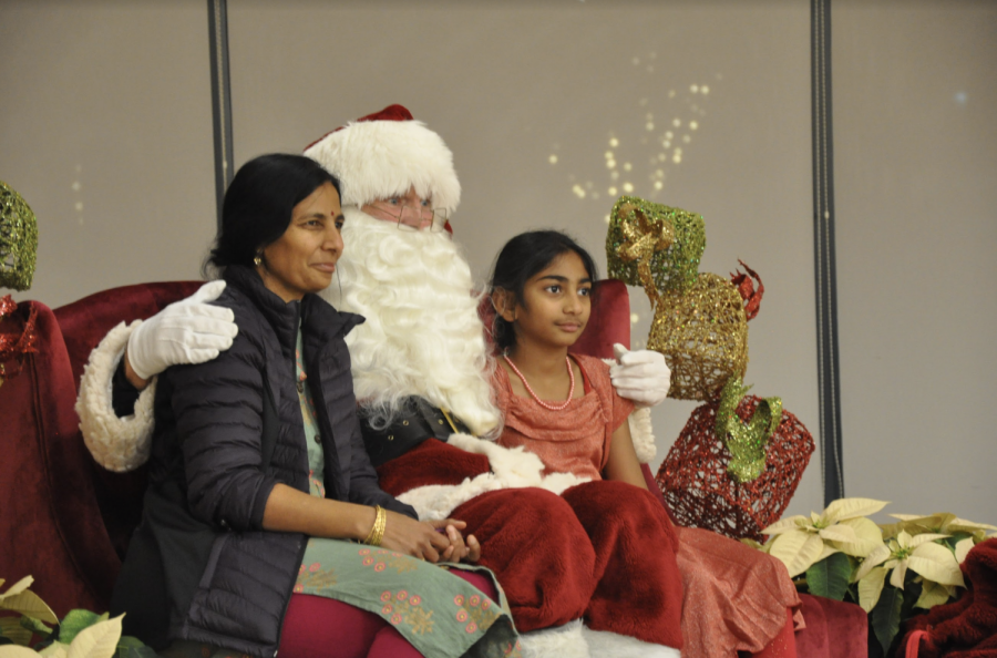 A parent and child pose with Santa after waiting in a 20-minute line to meet him.