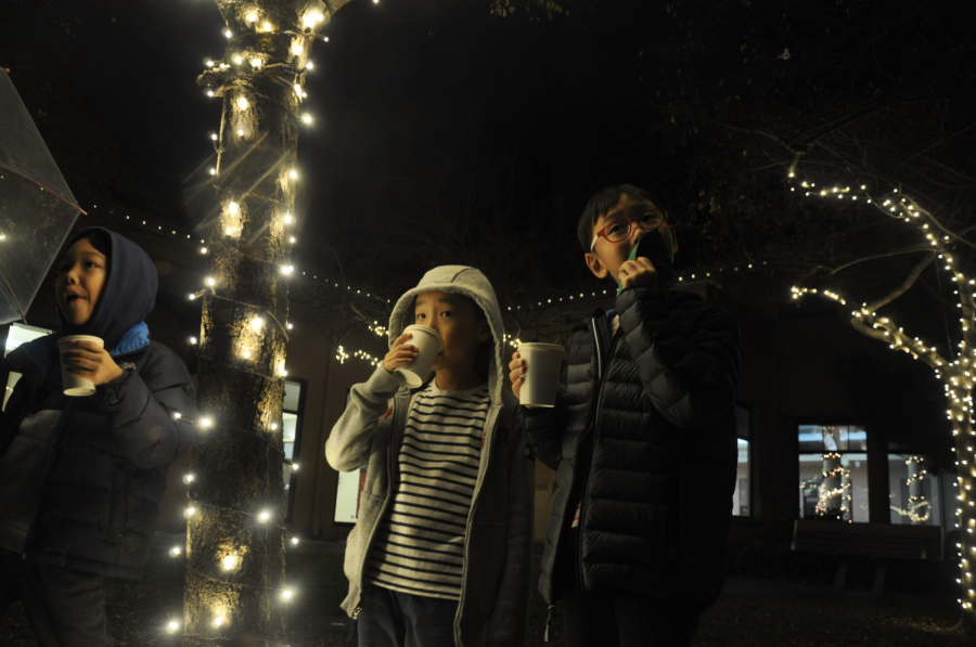 A group of kids drink their steaming hot chocolate next to the decorated trees around the Quinlan Center.