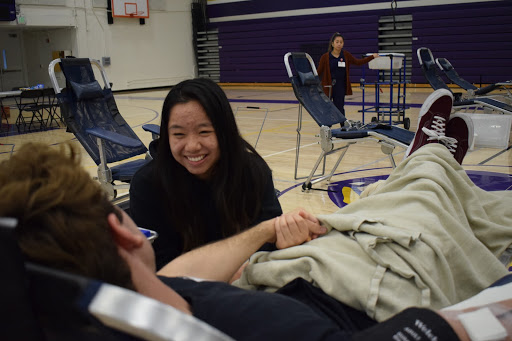 Senior Nate Reyes lies on his seat as he prepares for the procedure while holding on to senior Allison Wu, who smiles at him.