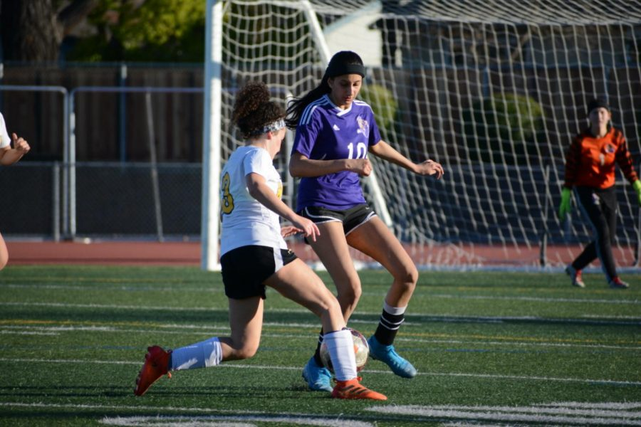 Junior Samiksha Rao attempts to bypass a WHS defender in the first half of the match despite their intense offensive plays. Junior Shriya Kaushik takes note on WHS' playing strategies during today's match especially.
