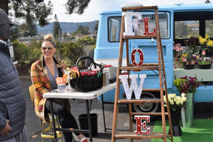 Founder Abi Lugo greets a passerby and answers questions about her flower shop on wheels.