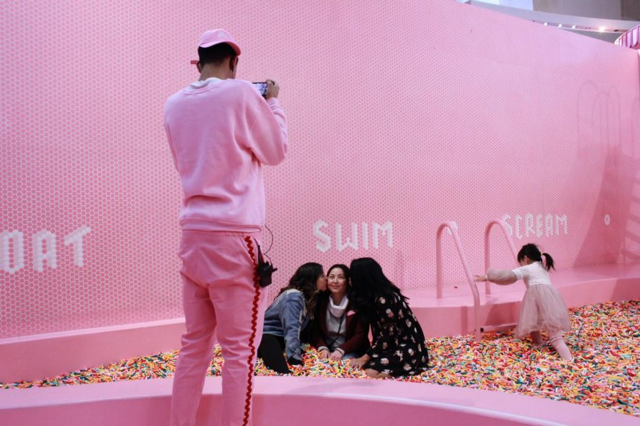 A staff member at the Museum of Ice Cream takes photos of visitors in the sprinkle pit.
