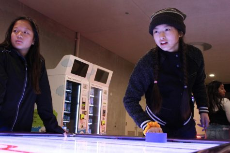 Freshman Amy Wu plays air hockey in the arcade center.