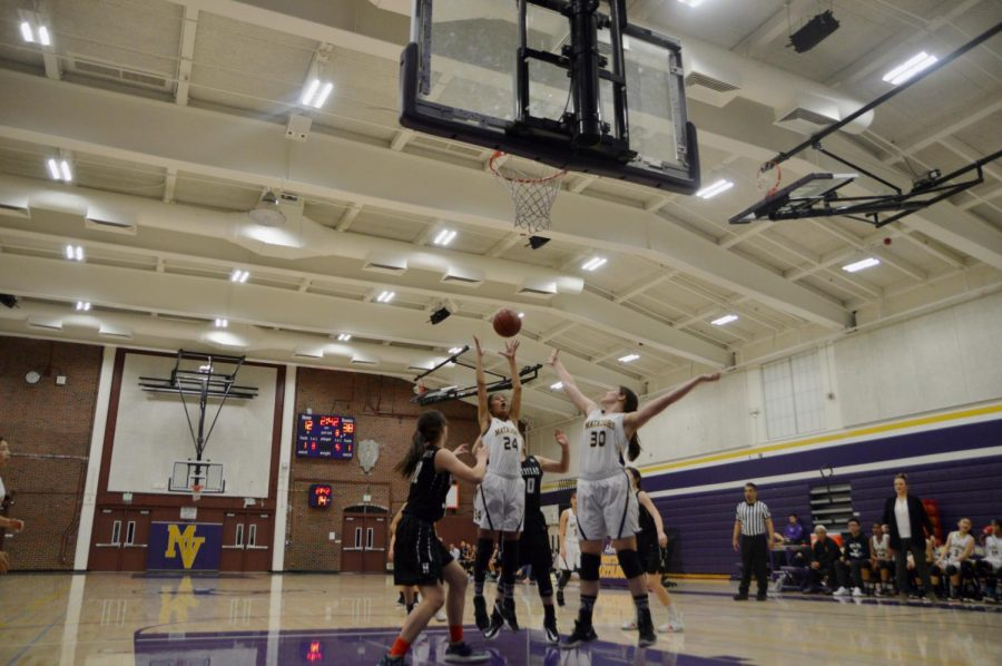 Junior Eshani Patel attempts to catch the ball after a rebounding shot off the hoop.