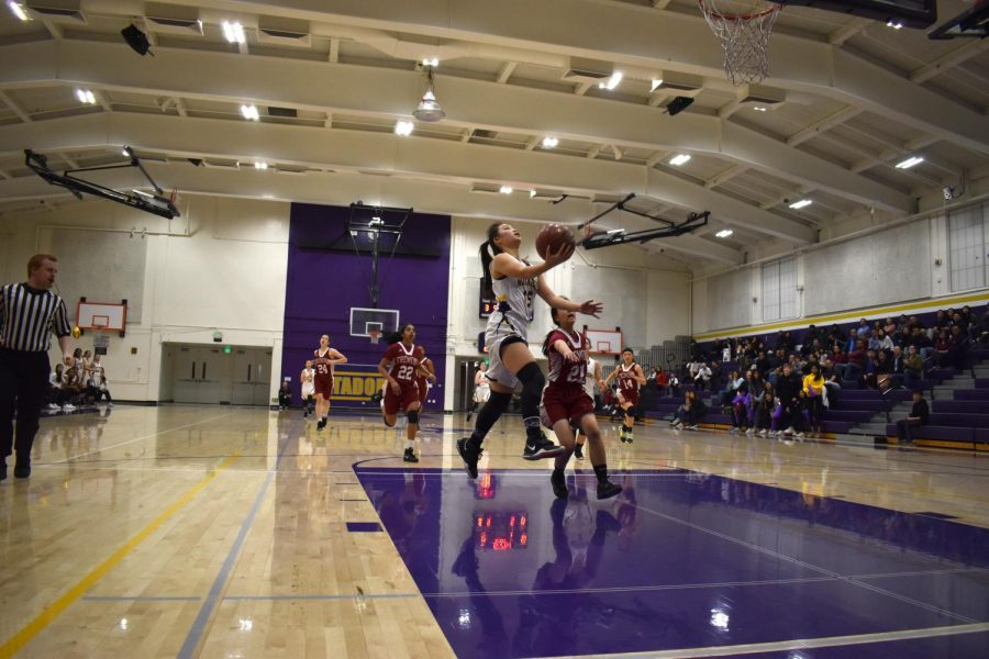 Senior Ashley Liu goes up for a layup, making the score 4-0 three minutes into the first quarter. Photo by Lance Tong